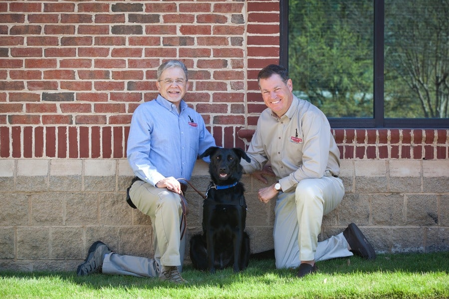 Bill Brightman with SD4V and John Hawkins, Owner and Founder of the Hawkins Law Firm pose with Darla, a service dog in training.
